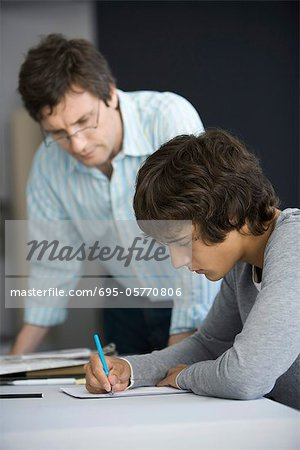 College student working on assignment, teacher assisting Stock Photo - Premium Royalty-Free, Image code: 695-05770806