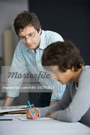 Teacher leaning on desk assisting student in classroom Stock Photo - Premium Royalty-Free, Image code: 695-05770807