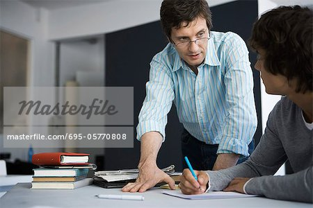 Teacher explaining assignment to student Stock Photo - Premium Royalty-Free, Image code: 695-05770808