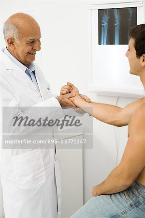 Doctor examining patient's wrist Stock Photo - Premium Royalty-Free, Image code: 695-05771247