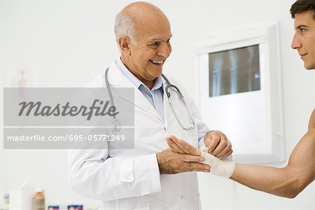 Doctor bandaging patient's wrist Stock Photo - Premium Royalty-Free, Image code: 695-05771249