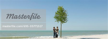 Children watering tree growing on beach Stock Photo - Premium Royalty-Free, Image code: 695-05771517