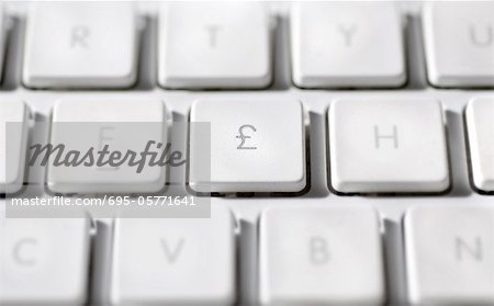 Great Britain Pound symbol on laptop computer keyboard Stock Photo - Premium Royalty-Free, Image code: 695-05771641