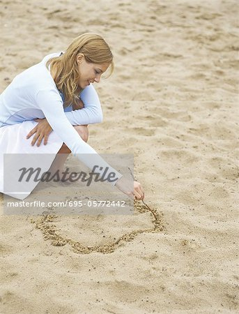 Woman drawing circle in sand, portrait Stock Photo - Premium Royalty-Free, Image code: 695-05772442