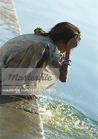 India, Sarkej, girl washing face by river Stock Photo - Premium Royalty-Free, Image code: 695-05772504