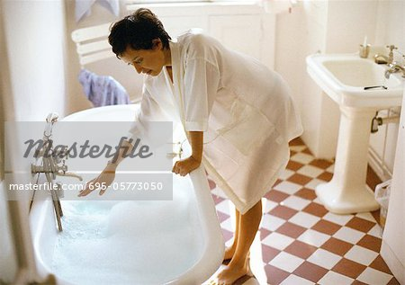 Woman bending over side of bathtub, hand under tap Stock Photo - Premium Royalty-Free, Image code: 695-05773050