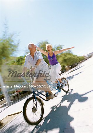 Mature couple riding together on tandem bike, woman holding her arms out, blurred