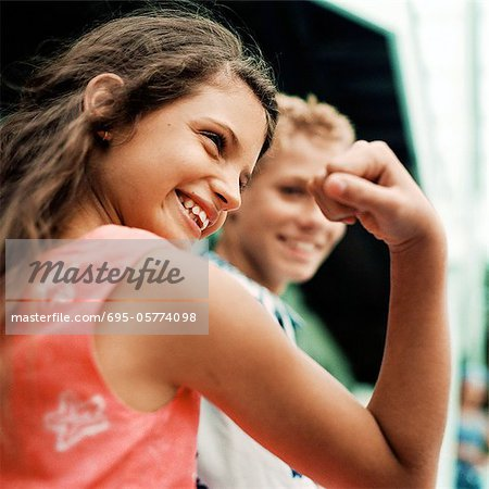 Girl flexing arm muscles, boy in background, smiling Stock Photo - Premium Royalty-Free, Image code: 695-05774098