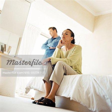 Man standing with arms crossed, behind woman sitting on edge of bed, low angle view Stock Photo - Premium Royalty-Free, Image code: 695-05774213