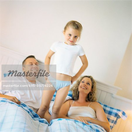 Girl standing between parents on bed Stock Photo - Premium Royalty-Free, Image code: 695-05774224