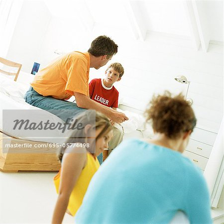 Parents and children sitting in bedroom, father having heart to heart conversation with son Stock Photo - Premium Royalty-Free, Image code: 695-05774498