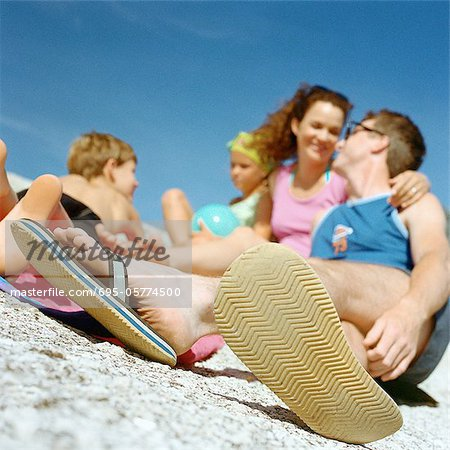 Couple and children on beach, focus on man's feet in foreground Stock Photo - Premium Royalty-Free, Image code: 695-05774500