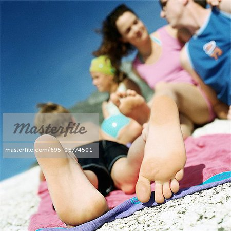 Couple and children lying on beach, focus on child's feet
