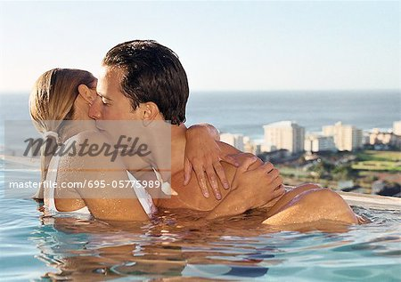 Couple kissing in swimming pool Stock Photo - Premium Royalty-Free, Image code: 695-05775989