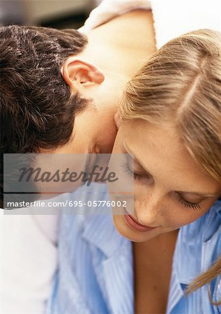 Man leaning over woman's shoulder, kissing woman's neck, close-up Stock Photo - Premium Royalty-Free, Image code: 695-05776002