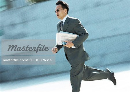 Businessman running outdoors Stock Photo - Premium Royalty-Free, Image code: 695-05776316