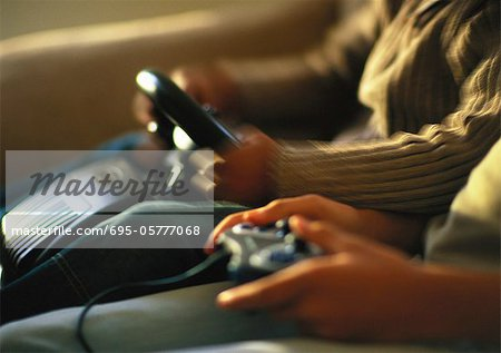 Hands of children playing video game, close up Stock Photo - Premium Royalty-Free, Image code: 695-05777068