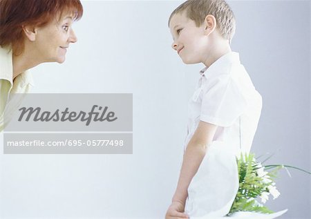 Boy surprising grandmother with bouquet of flowers Stock Photo - Premium Royalty-Free, Image code: 695-05777498