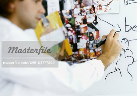 Man writing on board with images taped to it Stock Photo - Premium Royalty-Free, Image code: 695-05777802