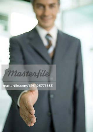 Businessman holding out hand for handshake Stock Photo - Premium Royalty-Free, Image code: 695-05778853