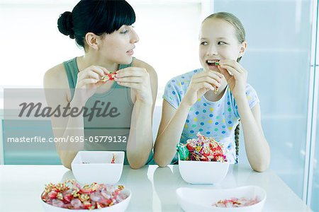 Young woman and preteen girl eating candy