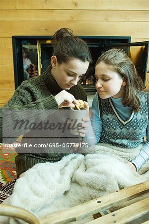 Two teenage girls sitting by fireplace, sharing snack Stock Photo - Premium Royalty-Free, Image code: 695-05779175