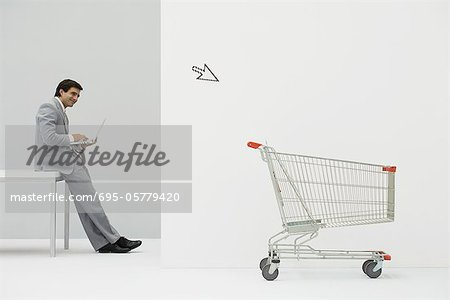Businessman leaning against desk, shopping online, cursor pointing at shopping cart Stock Photo - Premium Royalty-Free, Image code: 695-05779420