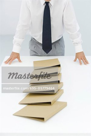 Binders lying on table after a chain reaction of being pushed over, cropped view of businessman Stock Photo - Premium Royalty-Free, Image code: 695-05779464