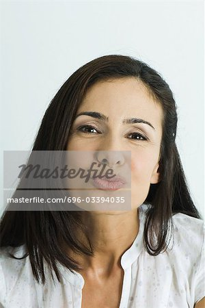 Woman puckering lips, looking at camera, portrait Stock Photo - Premium Royalty-Free, Image code: 696-03394035