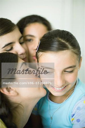 Young female friends kissing younger girl's cheek Stock Photo - Premium Royalty-Free, Image code: 696-03394076