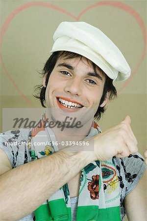 Young man wearing lipstick, cap, and scarf, smiling at camera, portrait Stock Photo - Premium Royalty-Free, Image code: 696-03394596