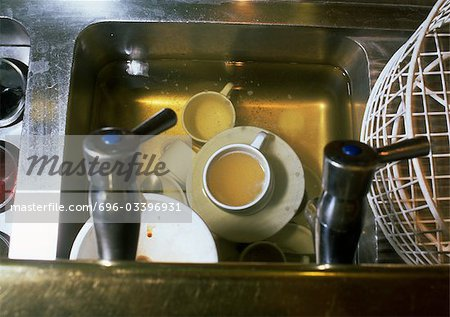 Dirty dishes soaking in water in sink, high angle view Stock Photo - Premium Royalty-Free, Image code: 696-03396931