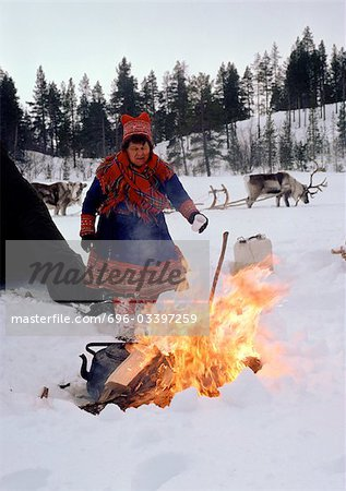Finland, Saami woman standing next to fire, sled reindeer in background Stock Photo - Premium Royalty-Free, Image code: 696-03397259