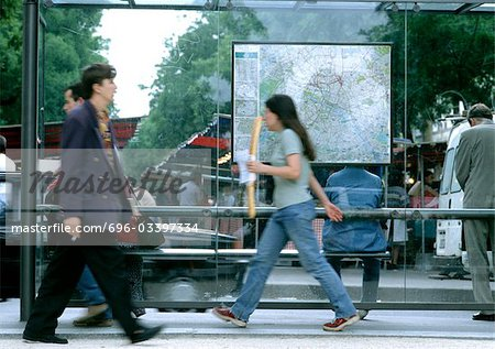 People walking past bus stop, blurred. Stock Photo - Premium Royalty-Free, Image code: 696-03397334