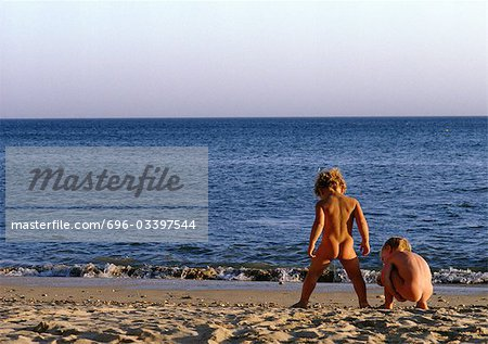Nude children playing on beach, rear view
