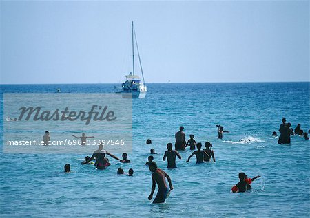 People wading in sea, sail boat in background Stock Photo - Premium Royalty-Free, Image code: 696-03397546