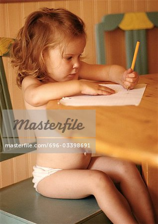 Little girl in underwear sitting at table, drawing Stock Photo - Premium Royalty-Free, Image code: 696-03398691