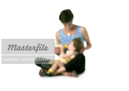Silhouette of woman feeding bottle to girl on lap, on white background, defocused Stock Photo - Premium Royalty-Free, Image code: 696-03399916