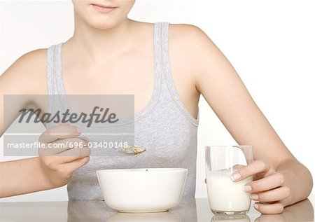 Young woman eating cereal Stock Photo - Premium Royalty-Free, Image code: 696-03400148