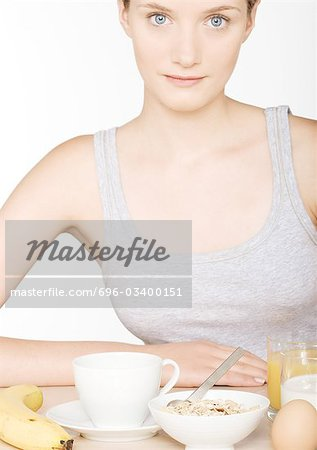 Young woman with large breakfast Stock Photo - Premium Royalty-Free, Image code: 696-03400151