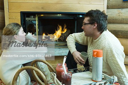 Young man and teenage girl sitting by fireplace, drinking hot beverages, looking at each other Stock Photo - Premium Royalty-Free, Image code: 696-03401813
