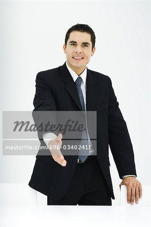 Businessman extending hand toward camera, smiling Stock Photo - Premium Royalty-Free, Image code: 696-03402411