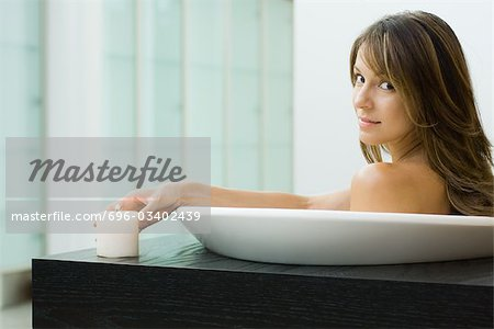 Woman sitting in bathtub, holding lit candle, smiling over shoulder at camera Stock Photo - Premium Royalty-Free, Image code: 696-03402439