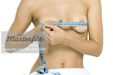 Nude woman wrapping measuring tape around breasts, cropped view Stock Photo - Premium Royalty-Free, Image code: 696-03402540