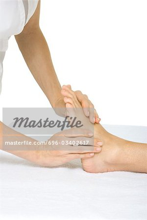 Woman receiving foot massage, cropped view Stock Photo - Premium Royalty-Free, Image code: 696-03402617
