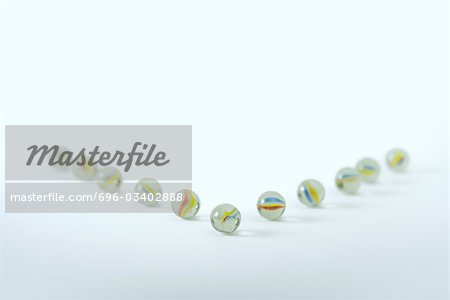 Marbles arranged to resemble arrow Stock Photo - Premium Royalty-Free, Image code: 696-03402888