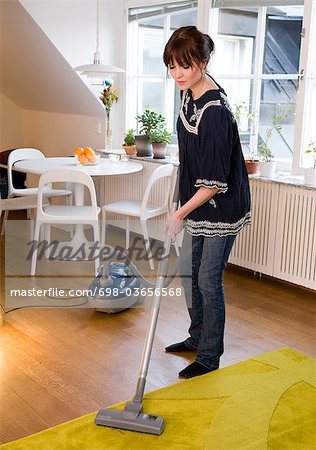 Woman vaccuming Stock Photo - Premium Royalty-Free, Image code: 698-03656568