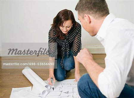Two colleagues looking at blueprints on floor Stock Photo - Premium Royalty-Free, Image code: 698-03656690
