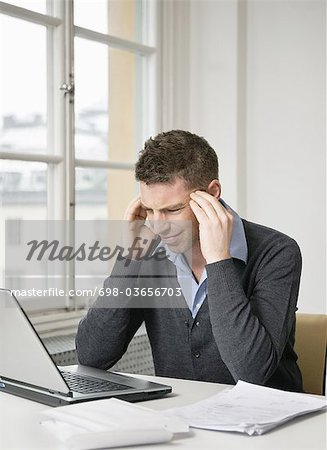 Troubled businessman using laptop Stock Photo - Premium Royalty-Free, Image code: 698-03656703