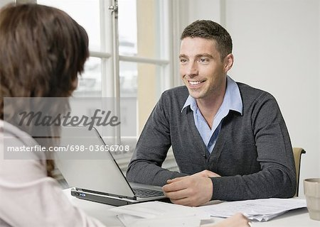 Two people talking at desk Stock Photo - Premium Royalty-Free, Image code: 698-03656708